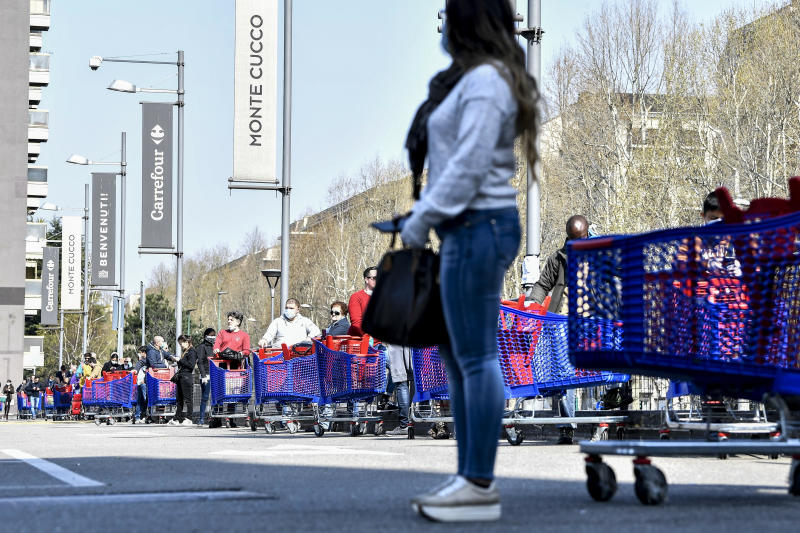 People queue waiting to enter a supermarket in Turin, Italy, Saturday, March 21, 2020. For most people, the new coronavirus causes only mild or moderate symptoms. For some it can cause more severe illness. (Marco Alpozzi/LaPresse via AP)