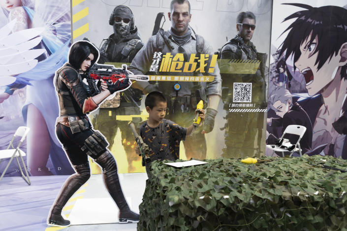 A child plays with a toy gun during a promotion for online games in Beijing on Saturday, Aug. 29, 2020. China is banning children from playing online games for more than three hours a week, the harshest restriction so far on the game industry as Chinese regulators continue cracking down on the technology sector. (AP Photo/Ng Han Guan)
