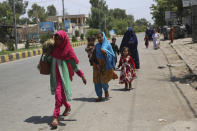 Afghan family leave their houses after an attack on a prison in the city of Jalalabad, east of Kabul, Afghanistan, Monday, Aug. 3, 2020. An Islamic State group attack on a prison in eastern Afghanistan holding hundreds of its members raged on Monday after killing people in fighting overnight, a local official said. (AP Photo/Rahmat Gul)
