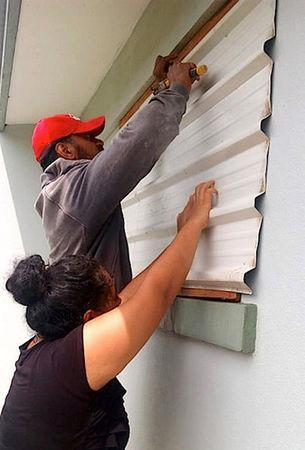 A supplied image shows locals covering windows to office buildings as part of preparations for Cyclone Gita in the Tonga capital of Nuku'alofa, February 12, 2018. Taniela Hoponoa/CARE Australia/Handout via REUTERS