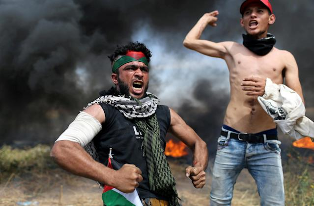 <p>Palestinian protesters react during clashes with Israeli troops at the Israel-Gaza border, in the southern Gaza Strip, April 2, 2018. (Photo: Ibraheem Abu Mustafa/Reuters) </p>