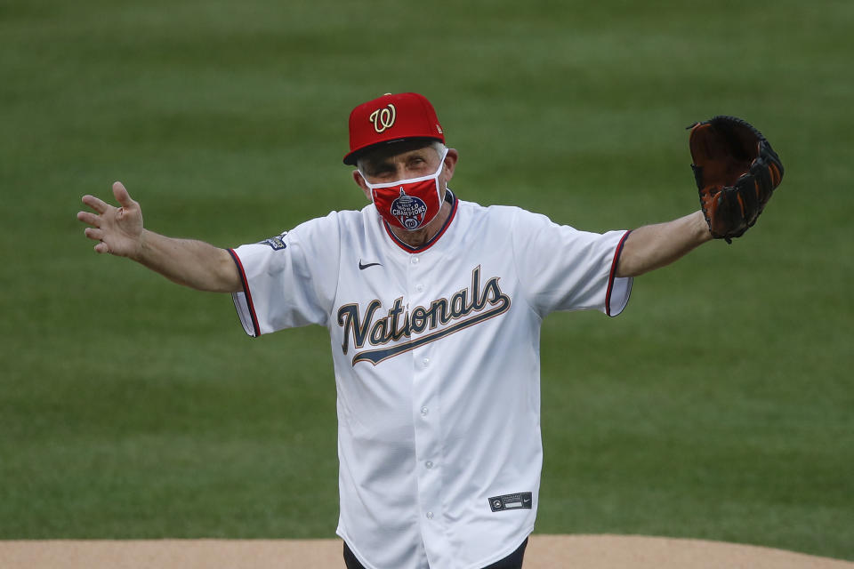 Dr. Anthony Fauci in a Washington Nationals jersey, mask and hat with a baseball glove raising his hands.