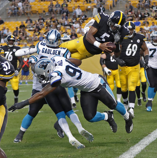 Pittsburgh Steelers quarterback Joshua Dobbs (5) leaps over Carolina Panthers defensive back Rashaan Gaulden (28) and defensive end Daeshon Hall (94) for a touchdown during the first half of a preseason NFL football game in Pittsburgh, Thursday, Aug. 30, 2018. (AP Photo/Keith Srakocic)