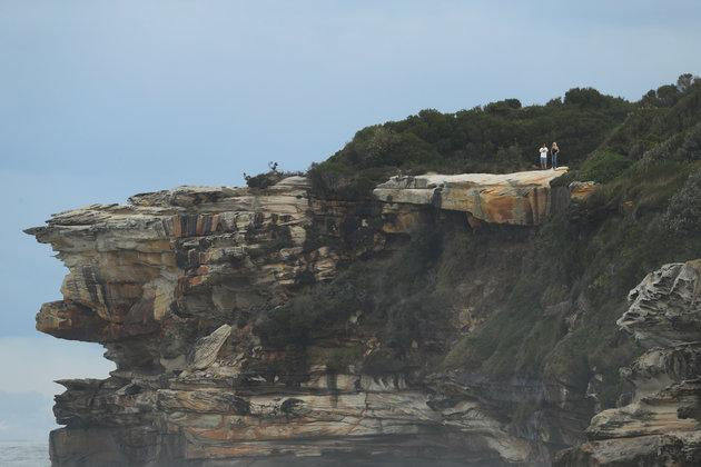 Spectators watch a surfing event from headland at Cape Solander