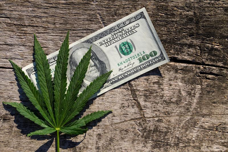 A pot leaf on a hundred-dollar bill on a wooden surface.