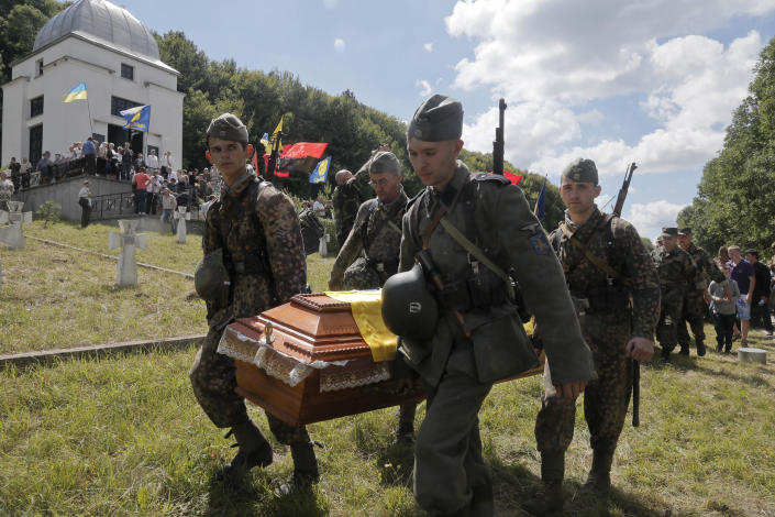 Ukrainians dressed in the SS Galychyna Division uniform carry a coffin with remains of the Division soldier on the SS Galichina Division cemetery near the village of Chervone in western Ukraine on Sunday, July 21, 2013. Western Ukraine marked the 70th anniversary of creation of the SS Galician Division. (AP Photo/Efrem Lukatsky)