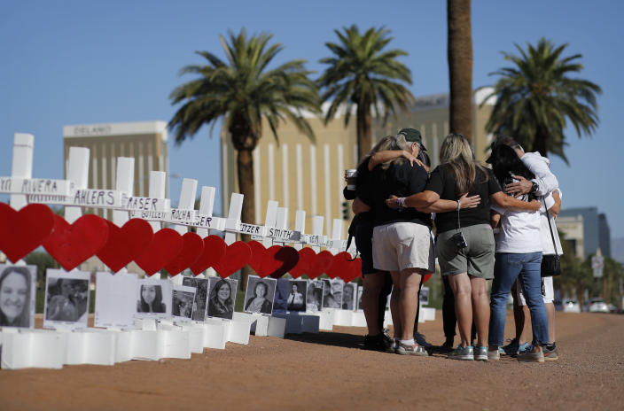 FILE - In this Oct. 1, 2019, file photo, people pray at a makeshift memorial for shooting victims in Las Vegas, on the anniversary of the mass shooting two years earlier. A panel planning a permanent memorial to the October 2017 shooting on the Las Vegas Strip made a nationwide call on Monday, March 1, 2021, for ideas about how best to remember the 58 people killed and thousands affected by the deadliest massacre in modern U.S. history. (AP Photo/John Locher, File)