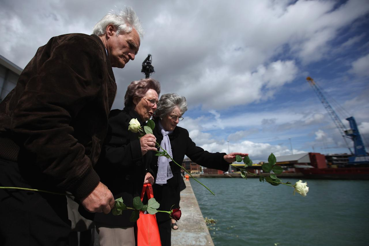 Friends and family of some of the descendants of those who perished when RMS Titanic sank, throw flowers into births 43 and 44 at Southampton Dock during a Centenary Memorial on April 10, 2012 in Southampton, England. The births mark the departure point of RMS Titanic when it set sail one hundred years ago today. The maiden voyage of the ill-fated passenger liner Titanic ended when she sank after hitting an iceberg in the Atlantic on the night of April 14, 1911 with the loss of 1517 lives.  (Photo by Dan Kitwood/Getty Images)
