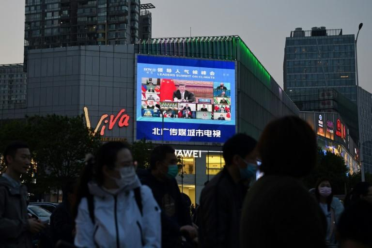 Pedestrians wait at an intersection as a news program report on Chinese President Xi Jinping's appearance at a US-led climate summit is seen on a giant screen in Beijing