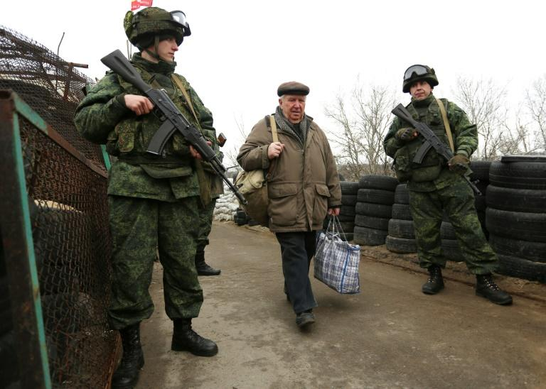 Pro-Russian rebels guard a checkpoint in Stanytsia Luhanska, Lugansk region, on March 7, 2017, as a man carrying bags passes into Ukraine-controlled territory