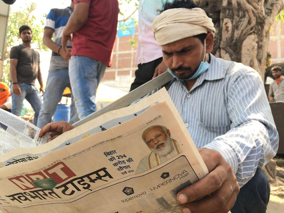 A daily wage earner reading newspaper at Noida Labour Chowk.
