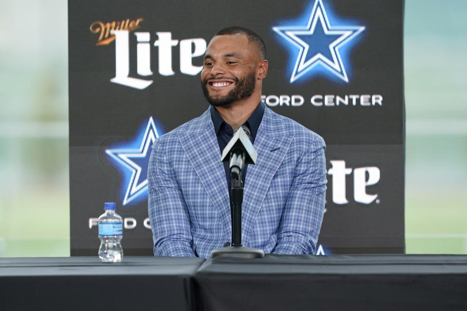 Dallas Cowboys quarterback Dak Prescott smiles during a news conference at the team's NFL football practice facility in Frisco, Texas, Wednesday, March 10, 2021. The Cowboys and Prescott have finally agreed on the richest contract in club history, two years after negotiations began with the star quarterback. (AP Photo/LM Otero)