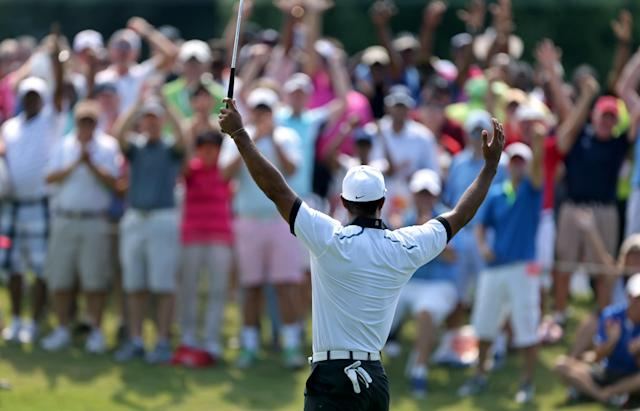 Tiger Woods celebrates with the crowd after making birdie on the third green during the second round of the Tour Championship golf tournament at East Lake Golf Club in Atlanta, Friday, Sept. 20, 2013. .(AP Photo/Atlanta Journal-Constitution, Jason Getz)