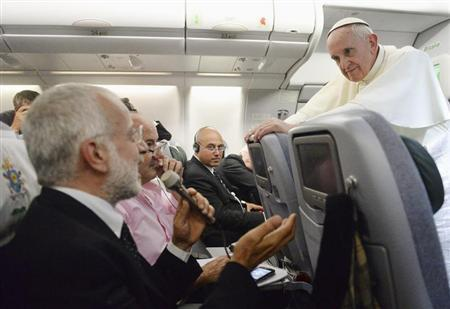 Pope Francis listens to journalist's questions as he flies back to Rome following his visit to Brazil