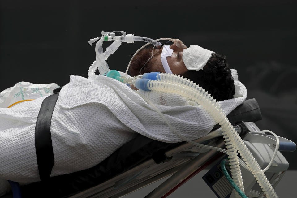 A 43-year-old patient suspected of having COVID-19 is transferred from an ambulance into the HRAN public hospital in Brasilia, Brazil, Wednesday, April 14, 2021. (AP Photo/Eraldo Peres)