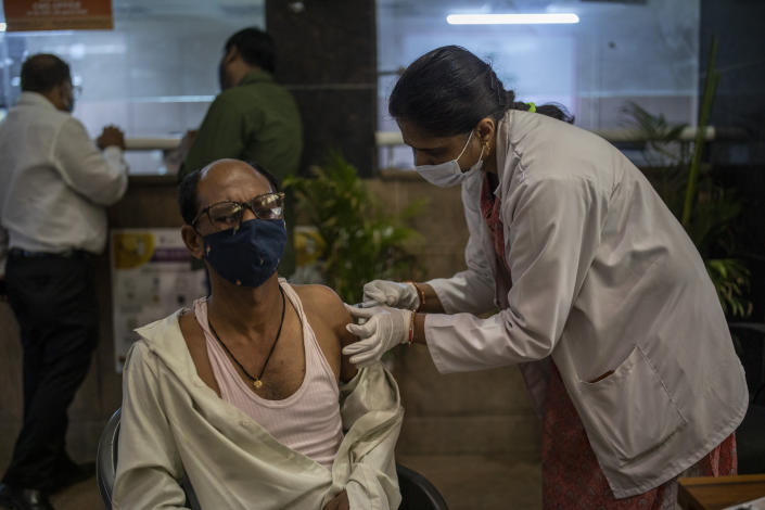 A man gets a COVID- 19 vaccine at a government hospital in Noida, a suburb of New Delhi, India, Wednesday, April 7, 2021. India hits another new peak with 115,736 coronavirus cases reported in the past 24 hours with New Delhi, Mumbai and dozens of other cities imposing night curfews to check the soaring infections. (AP Photo/Altaf Qadri)