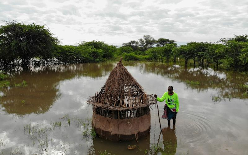 Farmer Parsaalach Nachaki, stands in the field where her house used to stand and is now submerged in rising water due to months of unusually heavy rains in lake Baringo, Kenya, - Baz Ratner/Reuters