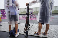 Satu Makela-Nummela, left, of Finland, with her coach, uses a protective rain cover for her shotgun before practice for the women's trap at the Asaka Shooting Range in the 2020 Summer Olympics, Tuesday, July 27, 2021, in Tokyo, Japan. (AP Photo/Alex Brandon)