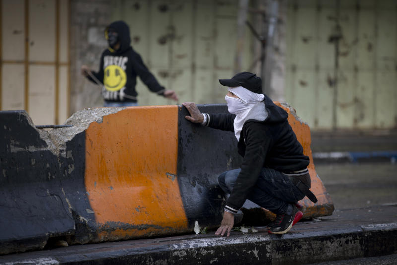 A Palestinian demonstrator take cover during clashes with Israeli troops in the West Bank city of Hebron, Monday, Dec. 9, 2019. Palestinian residents held a general strike to protest an Israeli plan to build a new Jewish neighborhood in the heart of the West Bank's largest city.   (AP Photo/Majdi Mohammed)