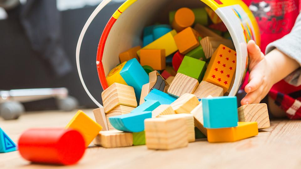 Small boy playing with wooden blocks on floor.