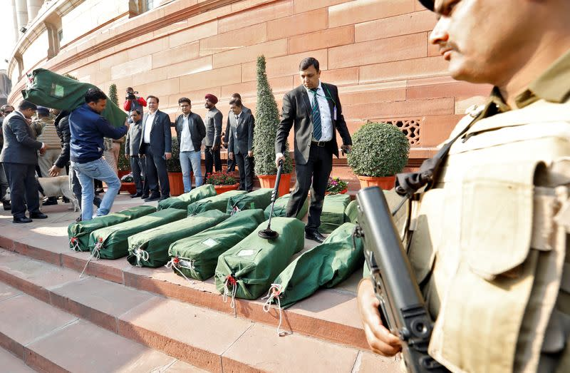 A security force personnel scans bags containing budget papers inside the Parliament premises in New Delhi
