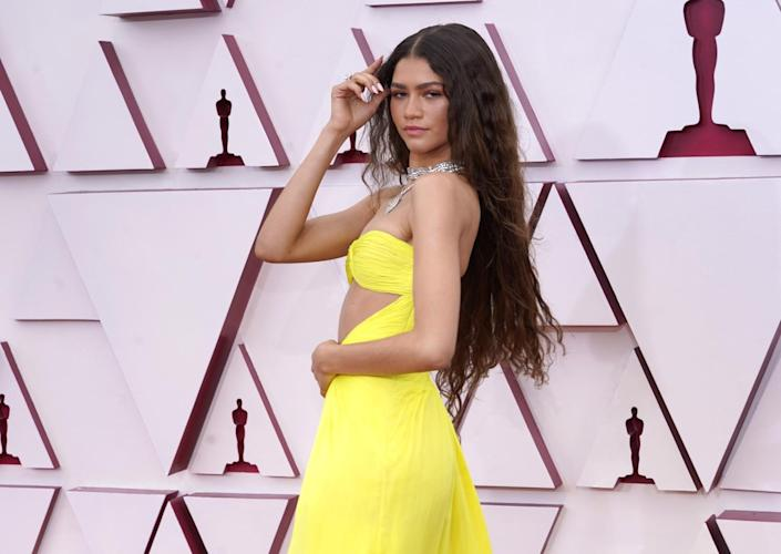 Zendaya wears a yellow gown with an exposed midriff.