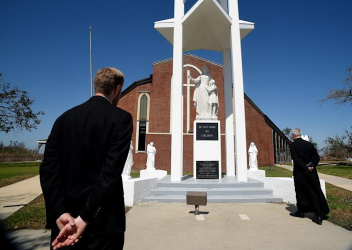 The Rev. Father D. B. Thompson, left, and Canon Jean-Marie Moreau look at the shrine of Our Lady Star of the Sea Catholic Church in Cameron, Louisiana, on Saturday, Oct.10, 2020.