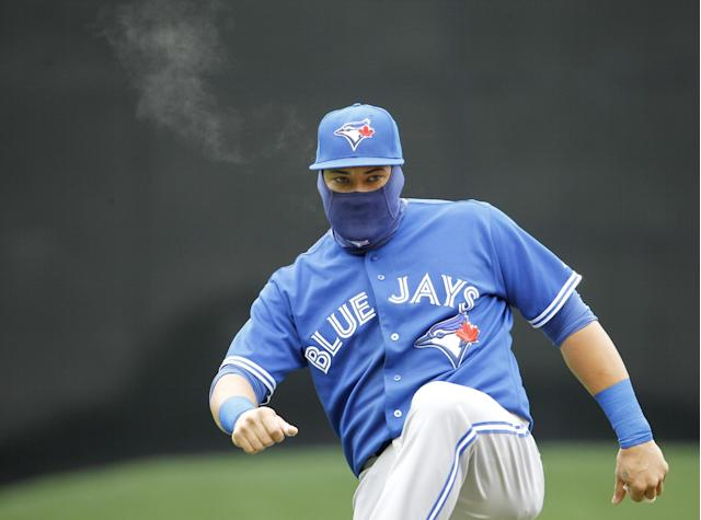 Toronto Blue Jays left fielder Melky Cabrera stretches in the cold before the first baseball game of a doubleheader against the Minnesota Twins in Minneapolis, Thursday, April 17, 2014. (AP Photo/Ann Heisenfelt)