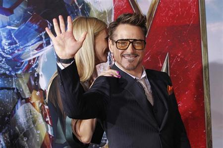 "Cast member Robert Downey Jr. waves next to co-star Gwyneth Paltrow at the premiere of ""Iron Man 3"" in Hollywood"