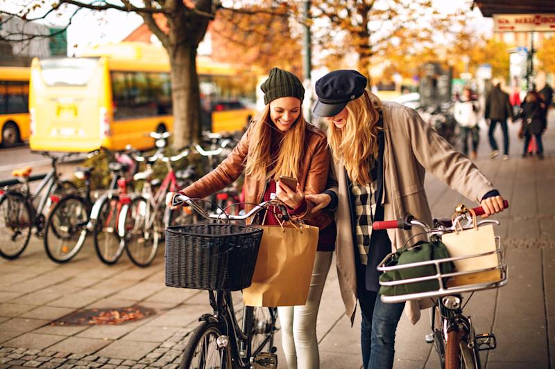 Close up of two friends leading their bicycles and using their phone