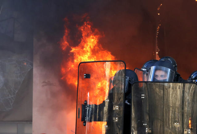 Riot police officers stand in front a burning building during a yellow vests demonstration Saturday, March 16, 2019 in Paris. Paris police say more than 100 people have been arrested amid rioting in the French capital by yellow vest protesters and clashes with police. They set life-threatening fires, smashed up luxury stores and clashed with police firing tear gas and water cannon (AP Photo/Christophe Ena)