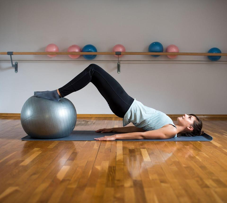 <p>Not only does this move strengthen your glutes and hamstrings, but it's also a fantastic move for engaging the lower abdominals. </p><p><strong>How to: </strong>Start lying down on the floor and place your feet up on the ball, arms resting alongside your body. Bring the ball closer to your body and come up into a bridge. Your heels should be gently pushing into the ball. From this position, keep your glutes elevated and straighten your legs, then bring them back into the bridge position. Lower your booty back down to the ground for a moment, then repeat.</p>