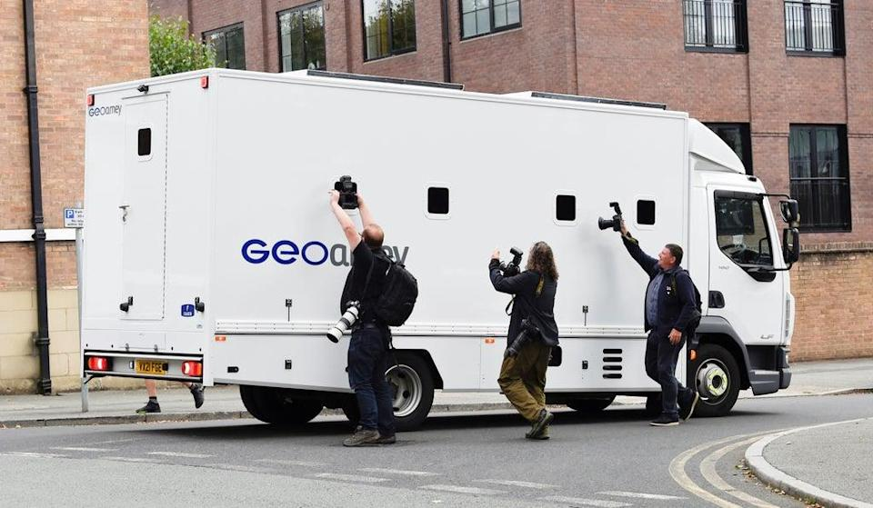Photographers take pictures through the windows of a prison van carrying Manchester City footballer Benjamin Mendy as it leaves Chester Magistrates' Court, Chester in August (PA) (PA Wire)