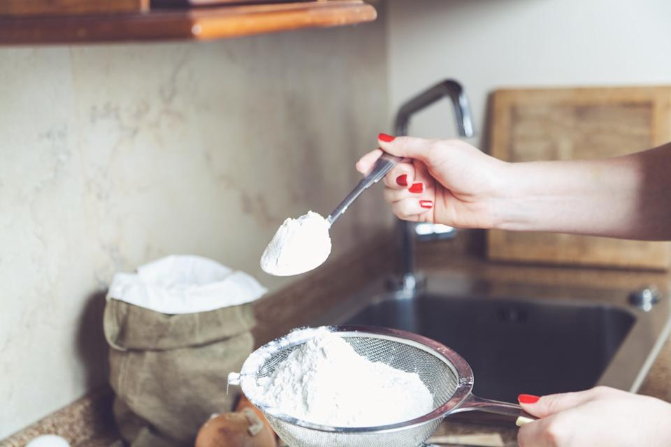 woman spooning flour into sieve