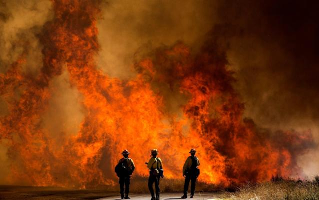 Firefighters watch as flames flare at the Apple Fire in Cherry Valley, California - AP Photo/Ringo H.W. Chiu