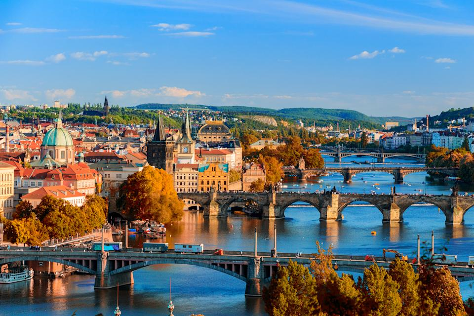 View of the Vltava River and Charle bridge with red foliage, Prague, Czech Republic. Photo: Getty