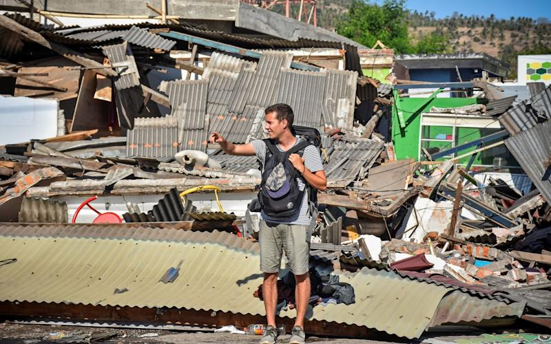 A foreign tourists stands near damaged buldings as he tries to flag down a car following a strong earthquake in Pemenang, North Lombok - ANTARA FOTO