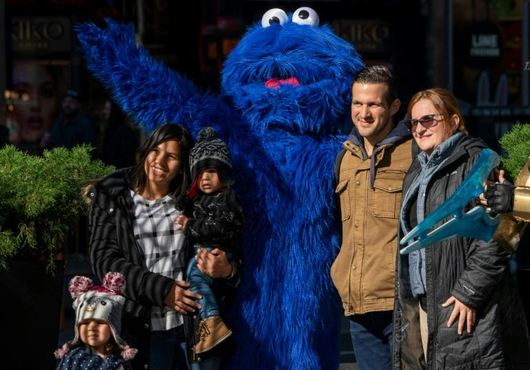 """A person dressed as """"Sesame Street"""" character Cookie Monster poses for a photo with tourists on 42nd Street"""