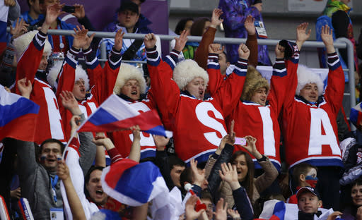 Hockey fans cheer for Russia during a men's ice hockey game against Slovenia at the 2014 Winter Olympics, Thursday, Feb. 13, 2014, in Sochi, Russia. (AP Photo/Julio Cortez)