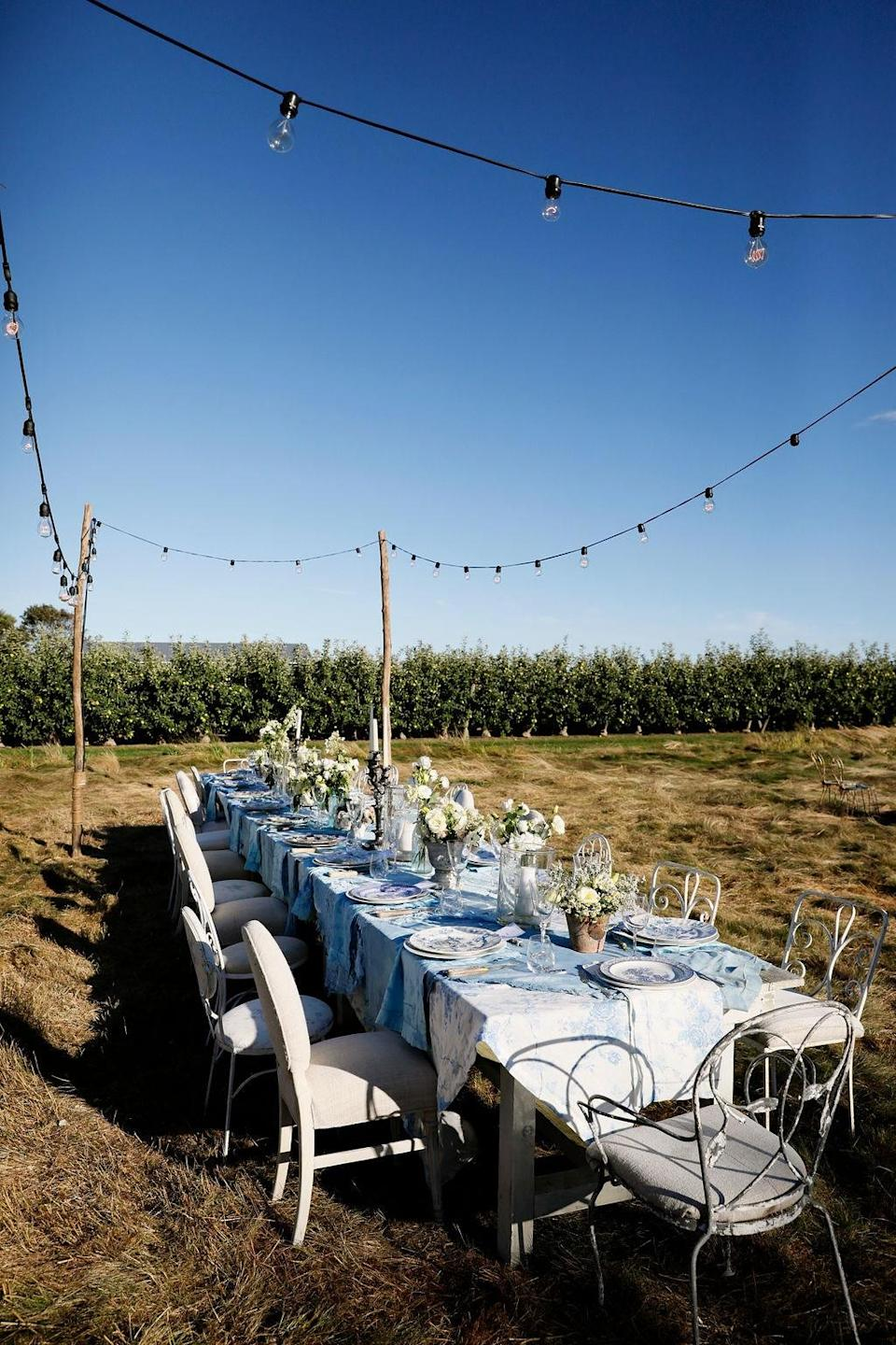 """""""Another view of the main farm table for the LoveShackFancy pod and family,"""" Nicholas says. """"Vintage indigo dyed lace draped over LoveShackFancy Home collection was the perfect balance of masculine and feminine."""""""