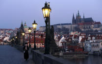 A woman with a covered face walks across the near empty Charles Bridge in Prague, Czech Republic, Thursday, April 2, 2020. The Czech Republic's government has approved further dramatic measures to try and stem the spread of the novel coronavirus called COVID-19. The coronavirus causes mild or moderate symptoms for most people, but for some, especially older adults and people with existing health problems, it can cause more severe illness or death. (AP Photo/Petr David Josek)