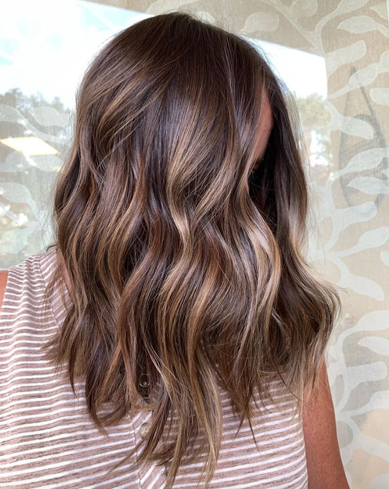 """According to Chicago colorist <a href=""""https://www.instagram.com/colorbyrex/"""" target=""""_blank"""">Rex Jimieson</a>, his clients have been moving away from the darker roots and lighter ends they've been loving in recent seasons. Instead, they've been asking for a look which Jimieson dubbed """"<a href=""""https://www.glamour.com/story/tweed-hair-color?mbid=synd_yahoo_rss"""">tweed hair</a>,"""" essentially subtle highlights that are evenly distributed. """"A contrast is still present, but not as 'overachiever' as seen in recent seasons,"""" he says. One of our favorite versions of the look? This rich brown with golden balayage pieces from <a href=""""https://www.instagram.com/simplicitysalon/"""">Simplicity Salon</a> in south Florida."""