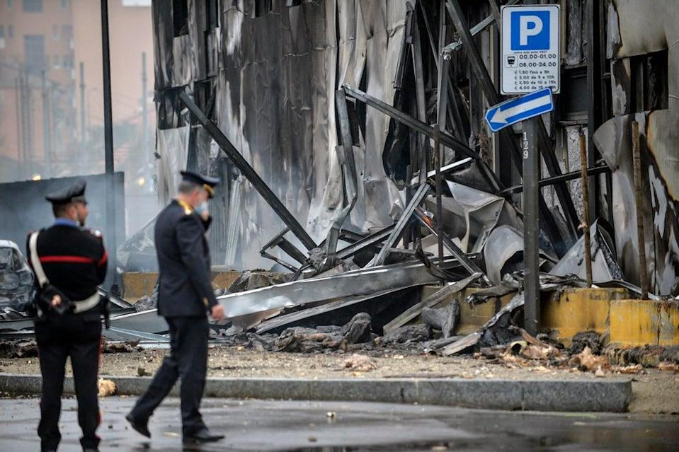 Carabinieri officers stand on the site of a plane crash, in San Donato (AP)