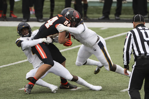 Oregon State tight end Teagan Quitoriano (84) is brought down by California safety Craig Woodson (26) and inside linebacker Kuony Deng (8) during the first half of an NCAA college football game in Corvallis, Ore., Saturday, Nov. 21, 2020. (AP Photo/Amanda Loman)
