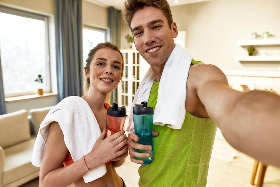 Young couple in sportswear smiling, while taking a selfie, showing healthy lifestyle after exercising at home. Fitness, workout and vlogging concept. Horizontal shot