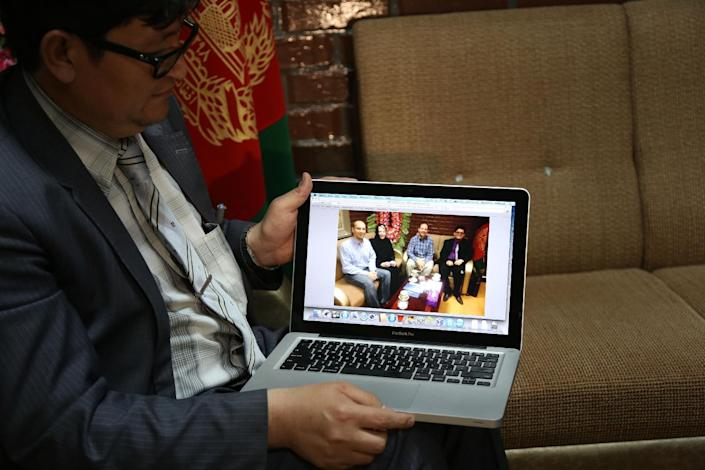 """Mohammad Hadi Hadayati, Kabul University's vice chancellor shows a photograph, from left, slain American Jon Gabel, his mother, his father Gary Gabel, who was also killed, and himself, during an interview with the Associated Press in Kabul, Afghanistan, Saturday, April 26, 2014. An Afghan police security guard opened fire on foreigners, on Thursday, April 24, 2014, as they entered the grounds of Cure International Hospital, killing three people, including pediatrician Dr. Jerry Umanos of Chicago. On Saturday, Kabul University vice chancellor Mohammad Hadi Hadayati identified the other two Americans killed in the attack as health clinic administrator Jon Gabel and his visiting father, Gary, also from the Chicago area. Jon Gabel's wife, also an American, was wounded, Hadayati said. """"We have lost a great man, a great teacher, a man who was here only to serve the Afghan people,"""" Hadayati said. Jon Gabel worked for the U.S.-based charity Morning Star Development and ran a health clinic at Kabul University, teaching computer science classes in his spare time, Hadayati said. Jon Gabel's parents were visiting from Chicago, and Hadayati had lunch with the whole family the day before the attack. (AP photo/Rahmat Gul)"""