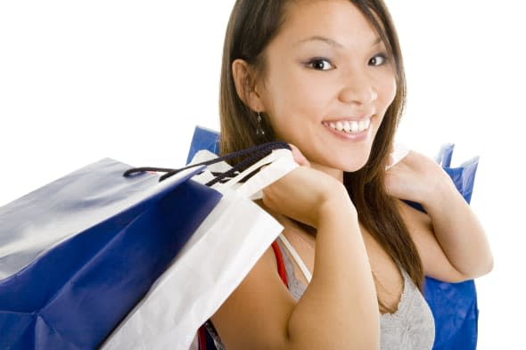 Young asian laughing woman carrying plenty of shopping bags