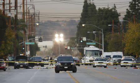 Police vehicles line the street around a vehicle (L) in which two suspects were shot following a mass shooting in San Bernardino, California December 3, 2015. REUTERS/Mike Blake