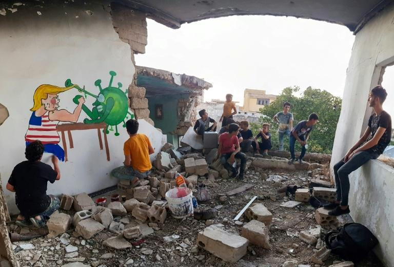 Syrian artist Aziz Asmar paints a mural depicting US President Donald Trump fighting with the coronavirus in October 2020 in Idlib province, which has remained a zone of fighting in the country's brutal war