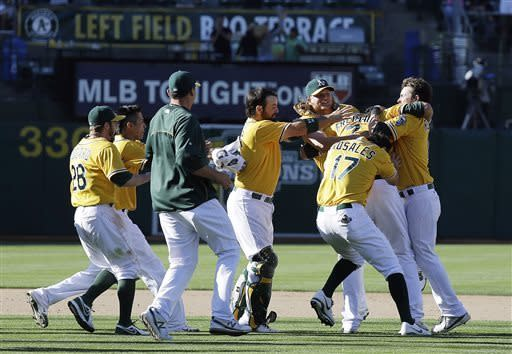 Oakland Athletics' Nate Freiman, second from right, is mobbed by his teammates after hitting the game-winning RBI single off New York Yankees pitcher Mariano Rivera in the 18th inning of a baseball game Thursday, June 13, 2013, in Oakland, Calif. Oakland won 3-2 in 18 innings. (AP Photo/Eric Risberg)